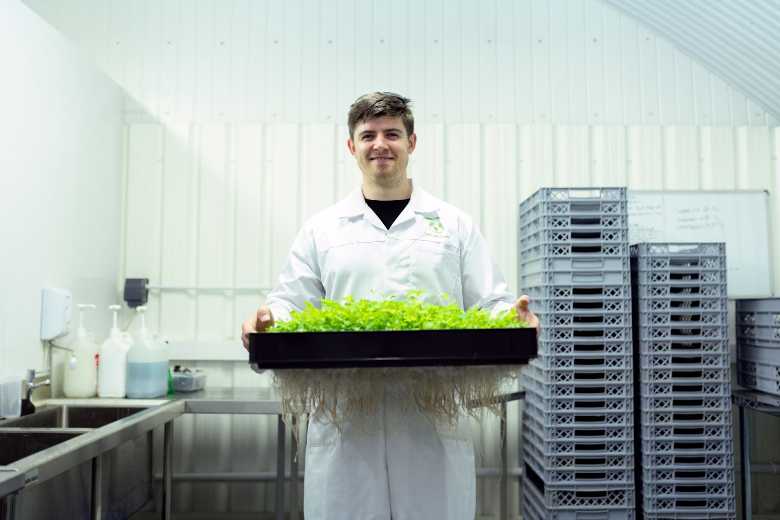 a man holding a tray of produce