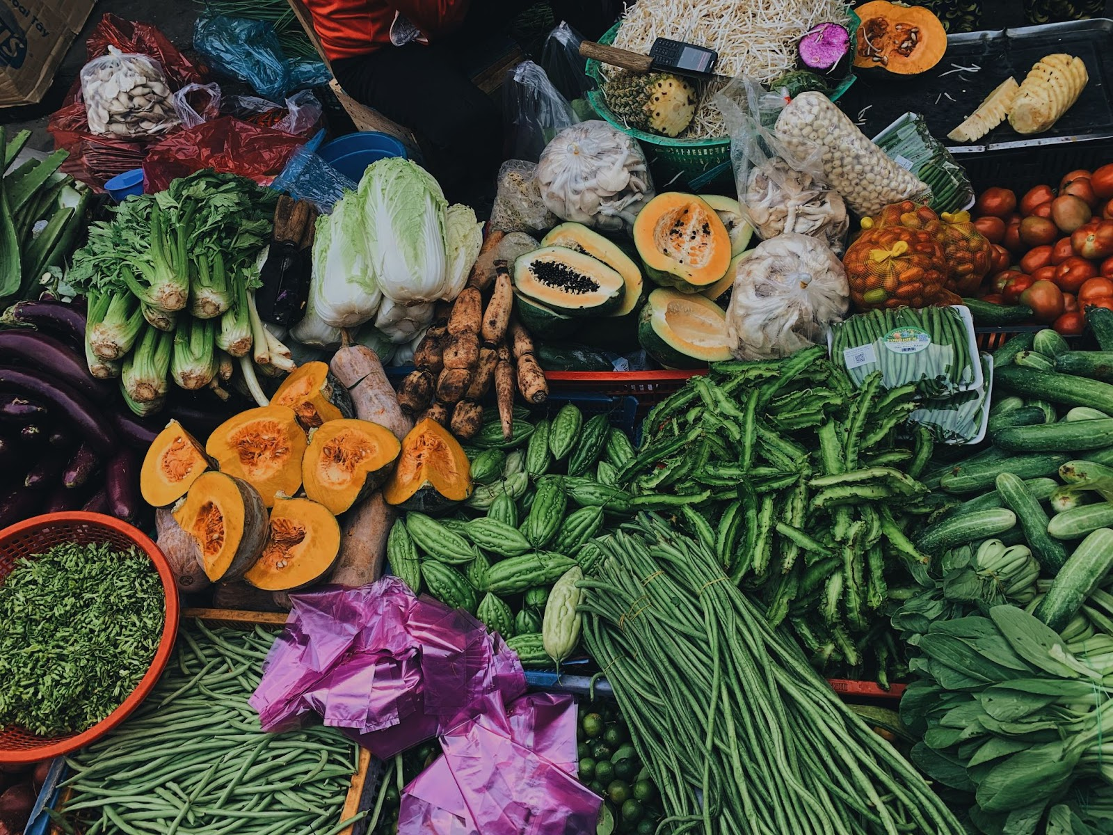 fruits and vegetables being sold on the sidewalk