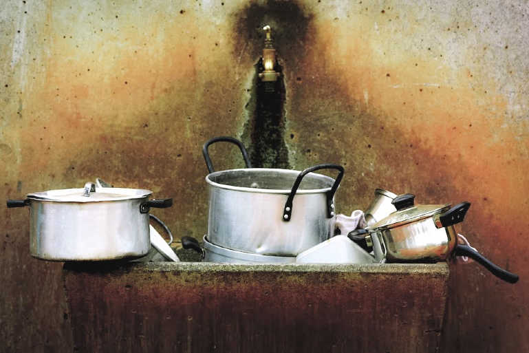use leftover coffee grounds to scour dirty pots and pans