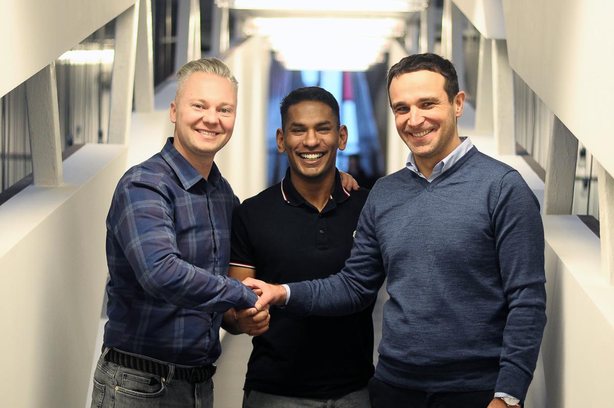 Three smiling men shaking their hands