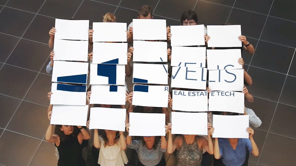 Velis logo on sheets of paper held by people