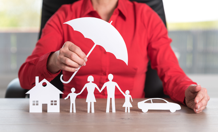 Insurance represented by umbrella over home, car and family