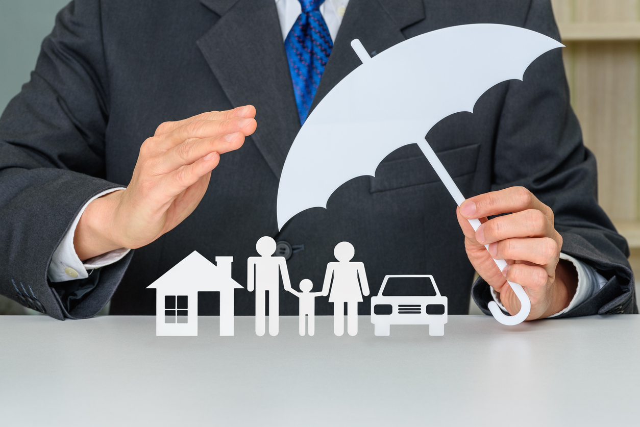 Insurance image represented by umbrella over home, car, and family