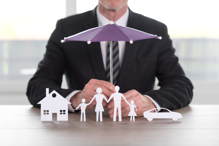 Insurance image represented by purple umbrella over house, car, and family