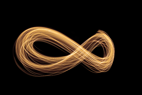 Golden light painting photography-infinite loop shape curve and metallic yellow light wave on black background.