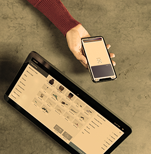 A woman using her virtual wallet to tap and pay for her coffee
