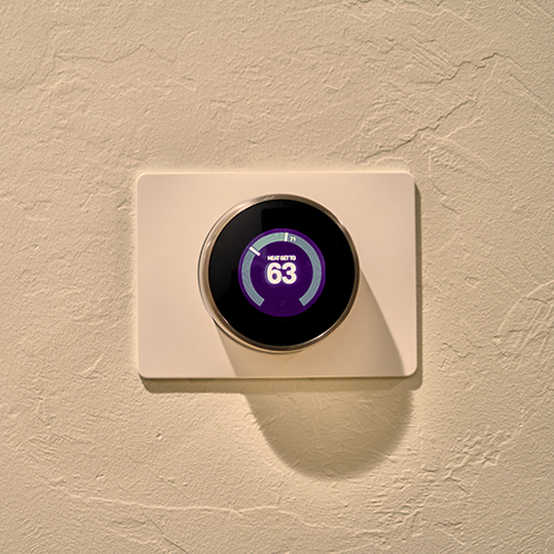 gray Nest thermostat displaying at 63 degrees fahrenheit.
