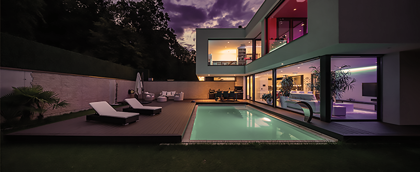 Modern villa with colored led lights at night. No one in it.