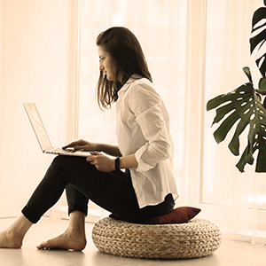 woman in a long sleeve shirt and pants sitting on a brown stiff beanbag as she takes an online visit with her doctor.