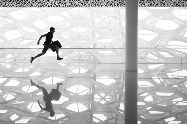 man holding a handbag as he runs across an empty building, identified as the shenzen airport in china.