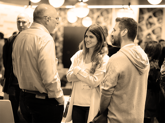 3 people, 2 men and 1 woman, talking at a networking event.