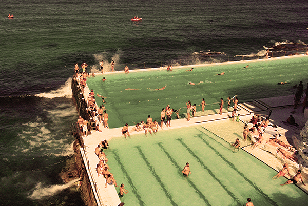 crow of people gathering at the swimming pool near bondi beach during the day.