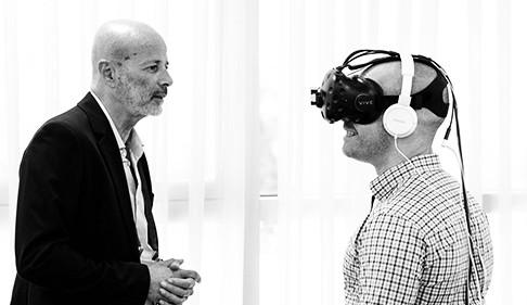 2 men at a tech conference. 1 person is trying the augmented reality/virtual reality glasses while the second person observes the individual and explains he should be experiencing.
