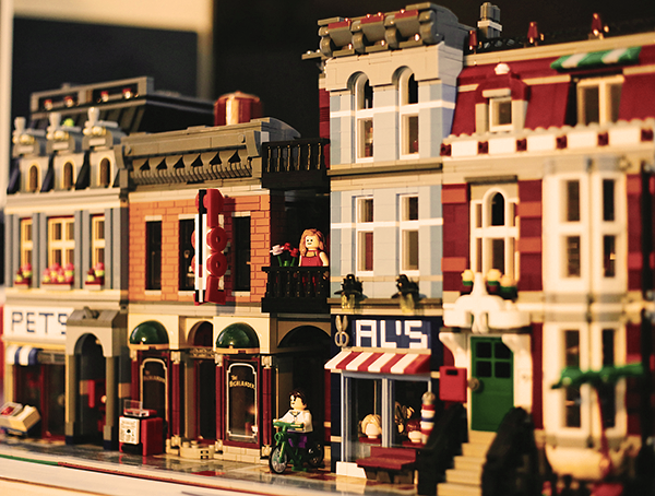 lego scale of a neighborhood with four building that are 3 stories tall. the woman lego is standing out on her 2nd floor balcony.