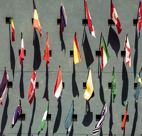 flags of 22 countries on a cement wall.
