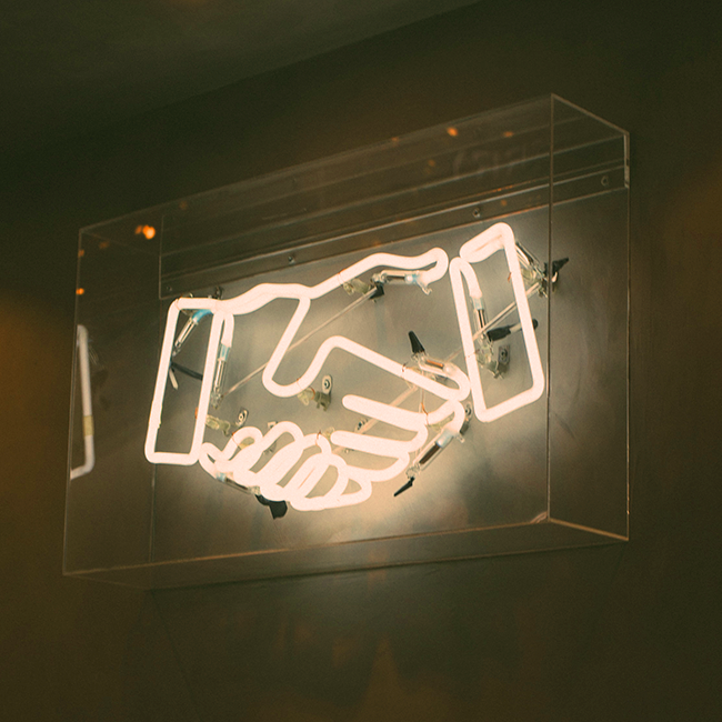 a neon sign symbolizing a corporation and startup agreeing to launch an ultra-personalized insurance product
