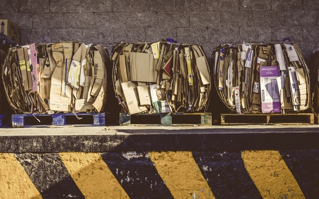 three piles of carboard industrial waste waiting on a curb for a waste management company