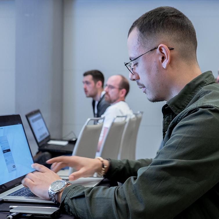 Uno de los alumnos del bootcamp de programación de HACK A BOSS preparando la presentación de su proyecto en el ordenador portátil para mostrar su proyecto en el Hacking Day.