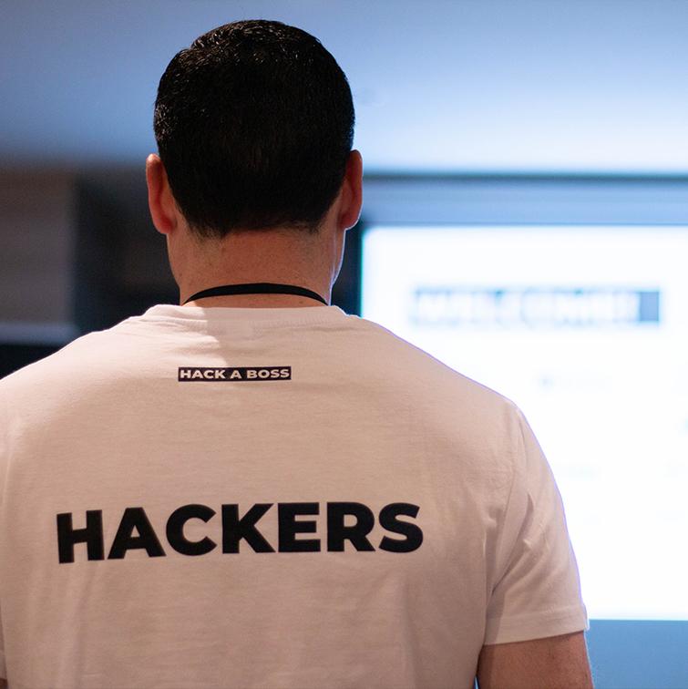 """Uno de nuestros alumnos de espaldas luciendo la camiseta de HACK A BOSS. Se puede leer la palabra """"HACKERS"""" en su espalda."""