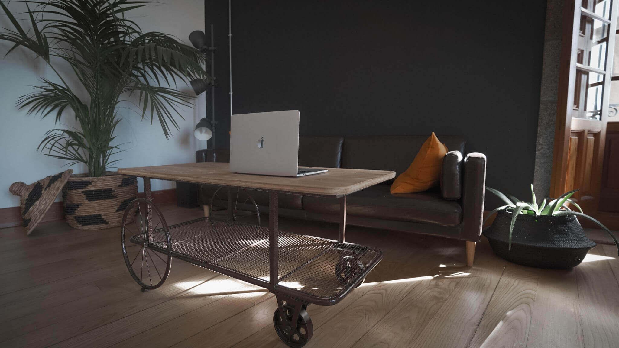 Interior de la oficina de HACK A BOSS en La Coruña. En concreto, una zona de descanso con un sofá y una mesa; además de otros elementos decorativos como plantas y cestas.