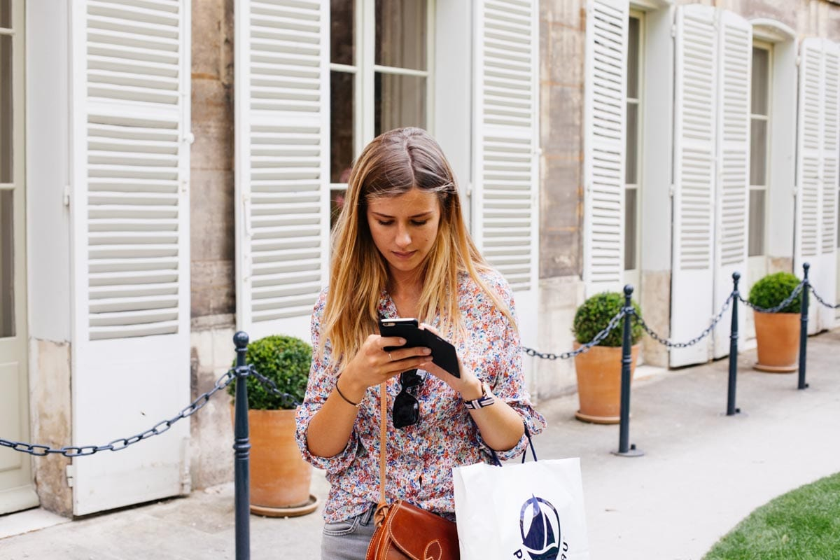 young woman texting outside while walking||||