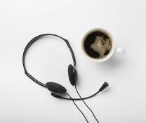 En kaffekopp och hörlurar