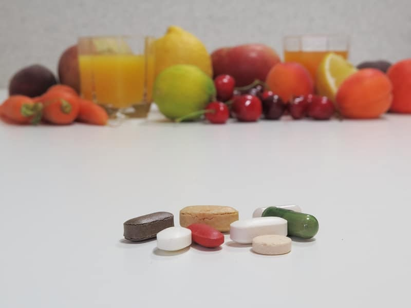 Vitamins placed in front of a pile of fruit.