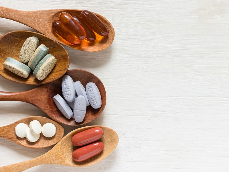 Vitamins placed on wooden spoons.