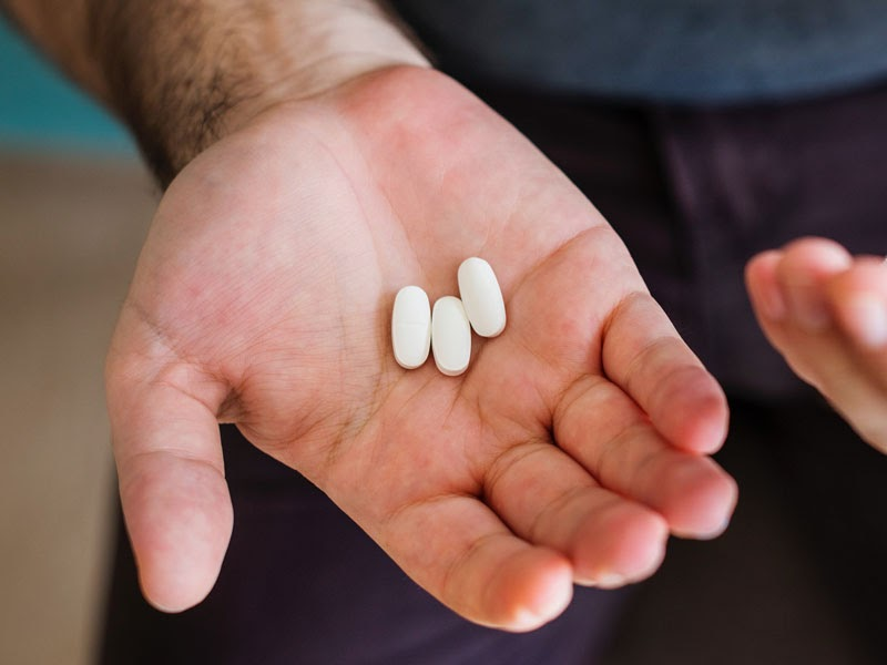 A man holding three pills.