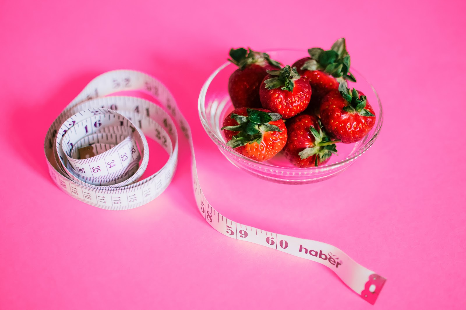 A waist measuring tap next to a bowl of strawberries