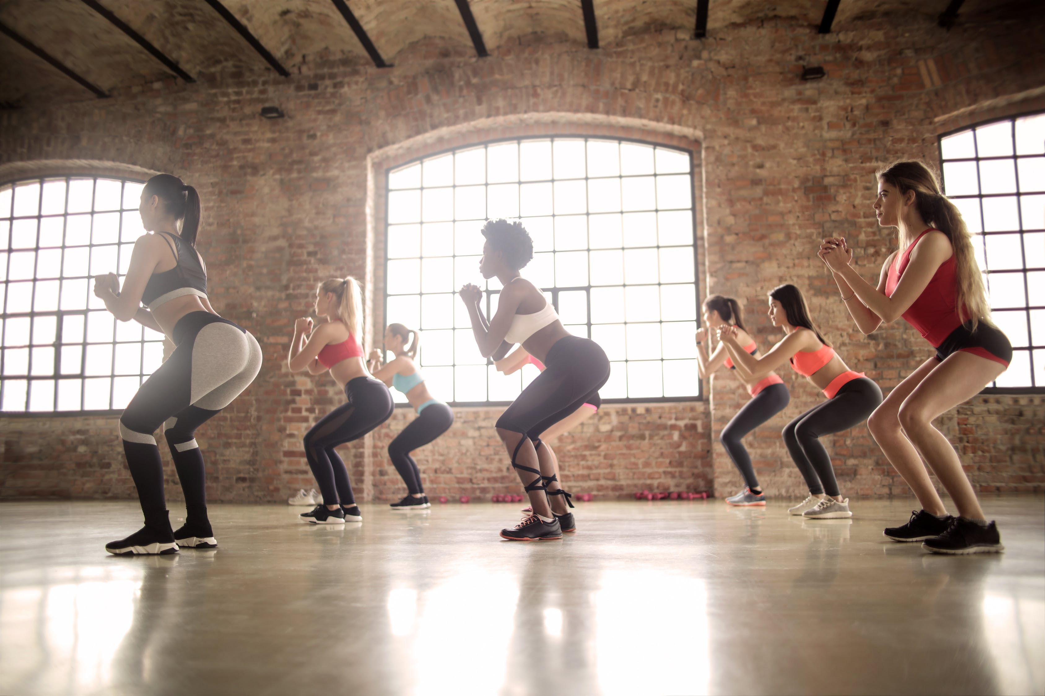 Women squat in unison during an exercise class.