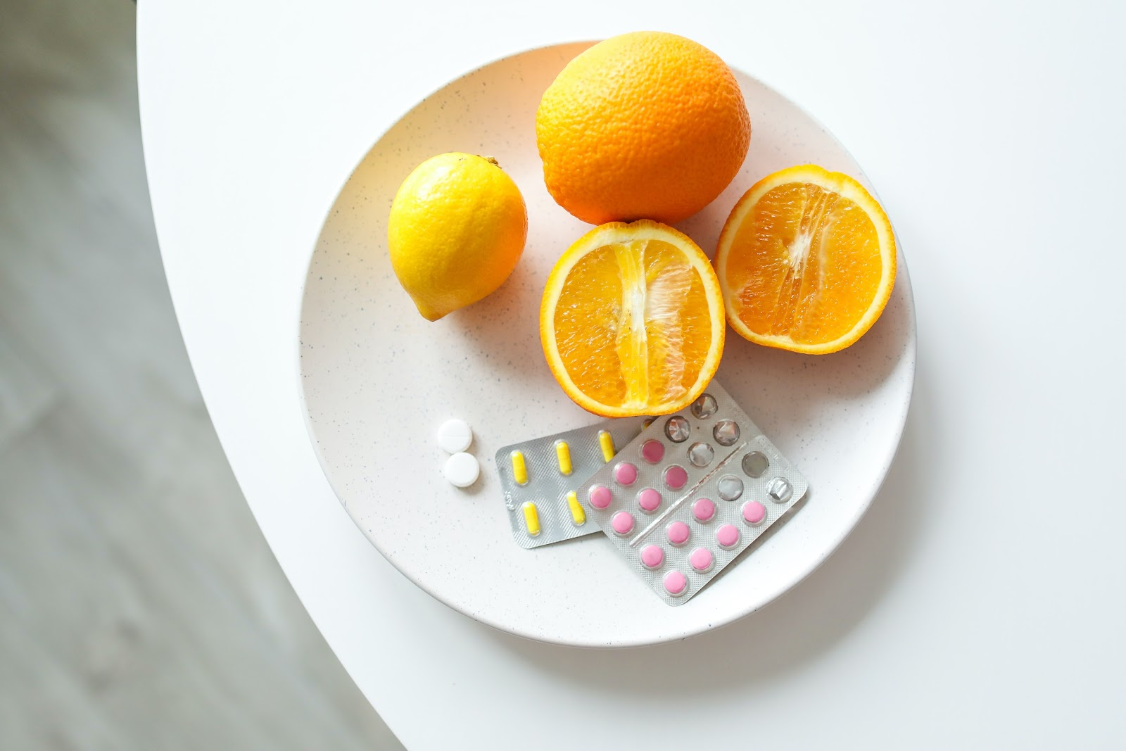 Slice and unsliced orange, and  a lemon with a packet of pills on a white plate