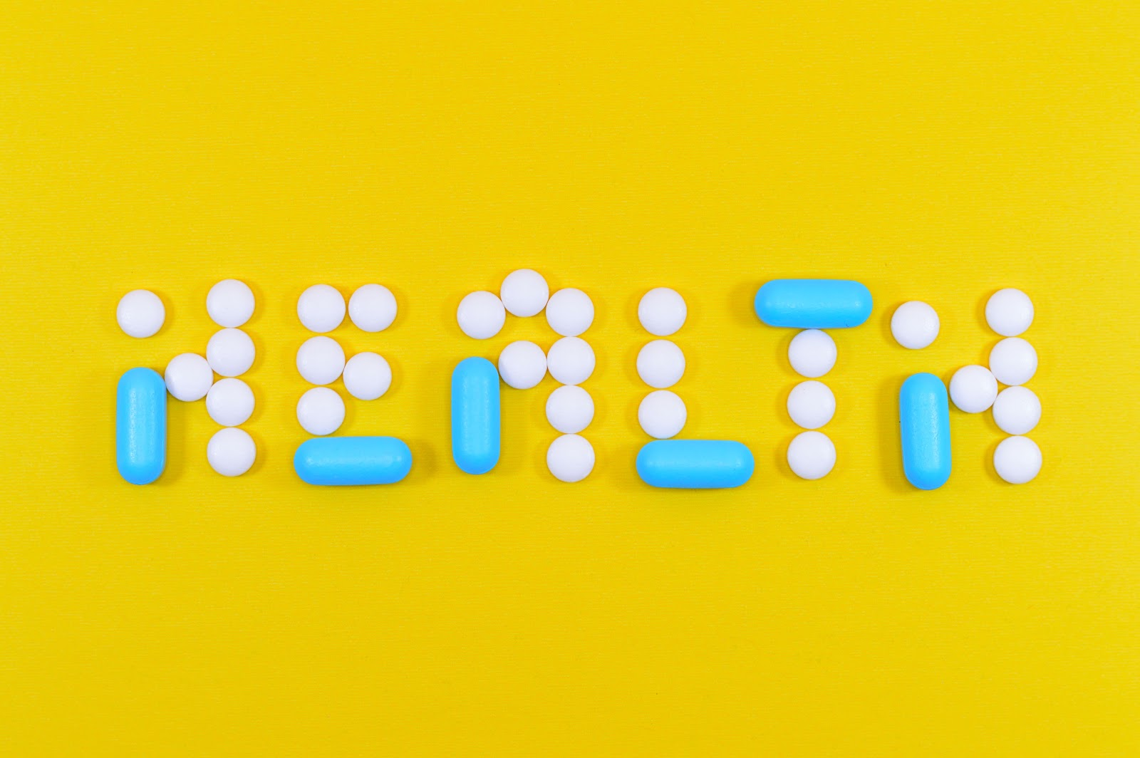 Supplements spelling out the word health atop a yellow background