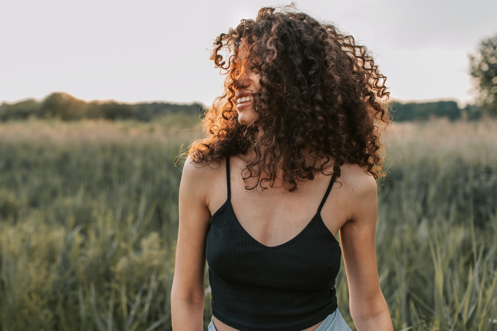 A curly haired woman laughing in a grass field