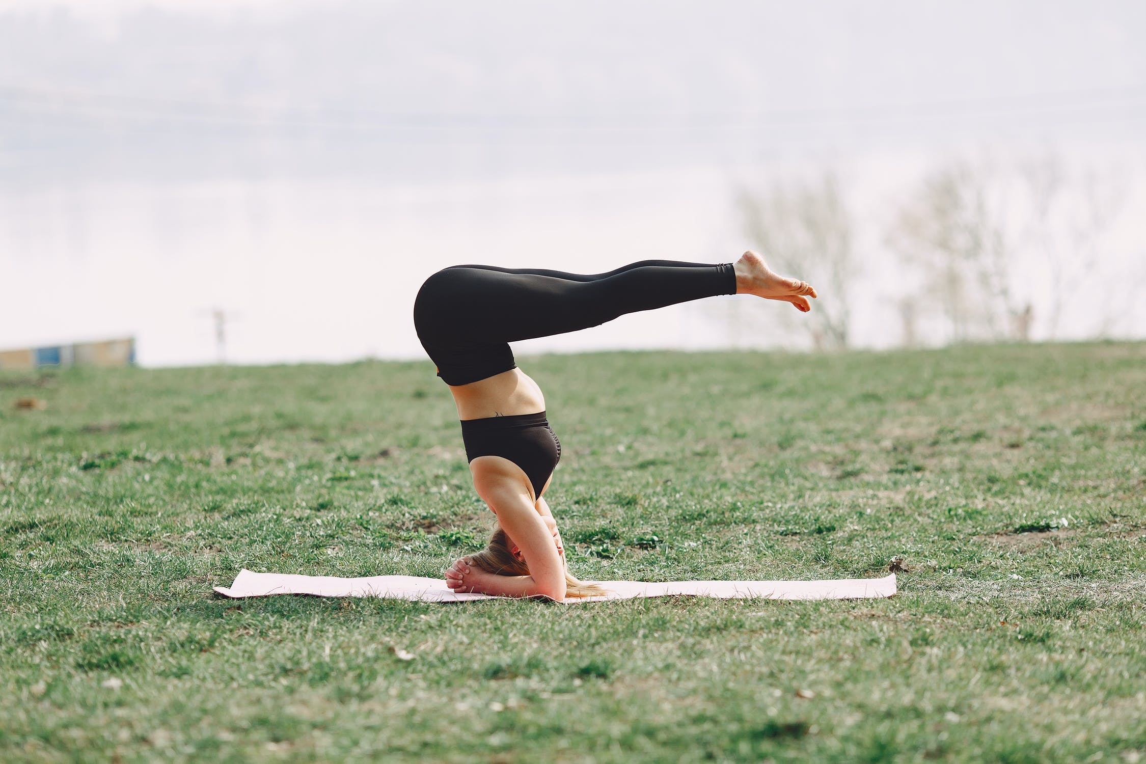 A woman performs a difficult yoga pose on a mat in the park.