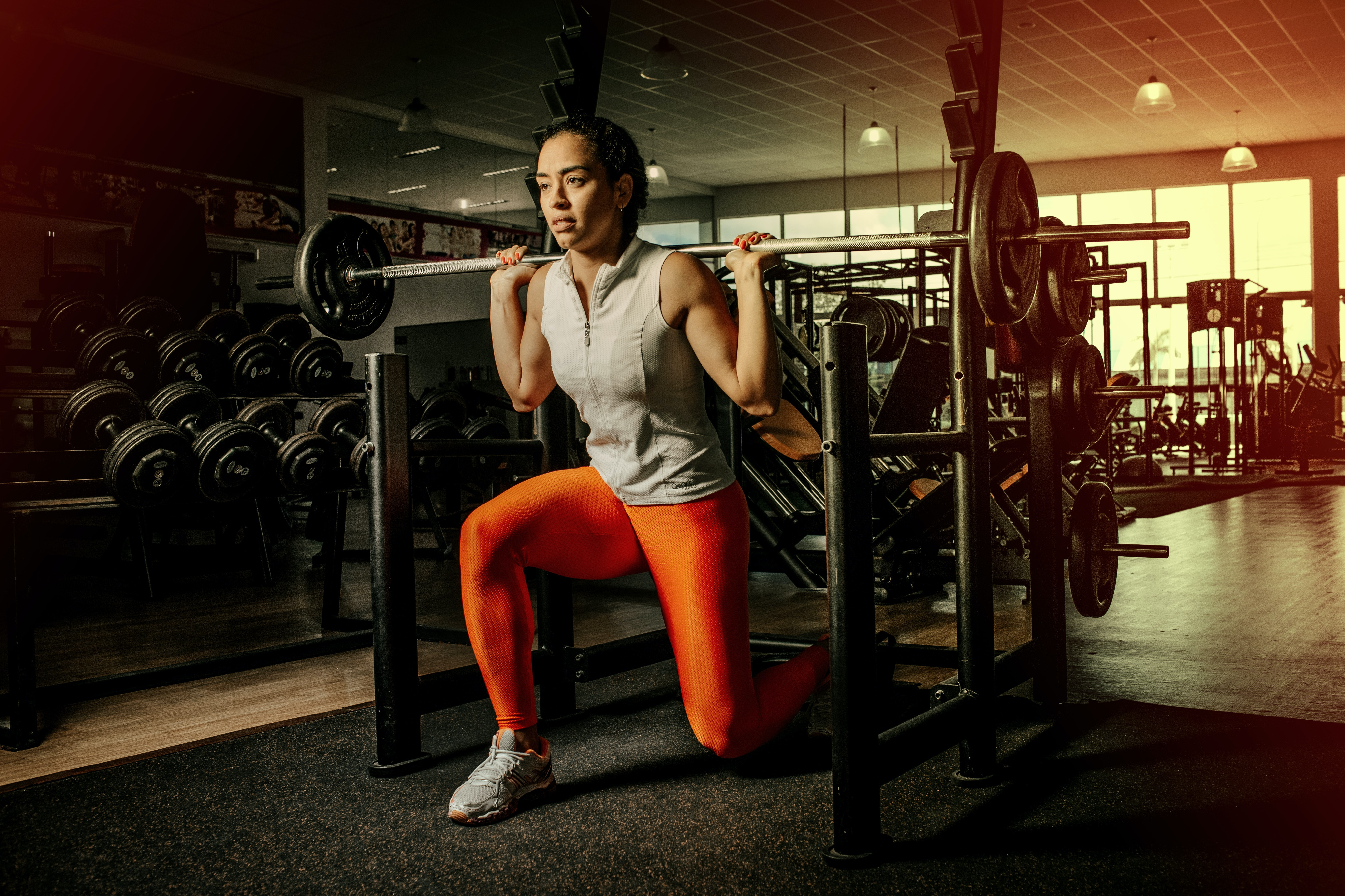 A woman lunges with a barbell in an empty gym.