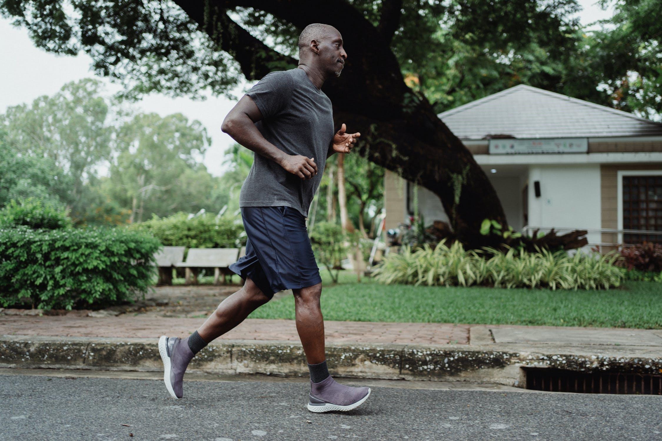 A man jogs down the street of a neighborhood.