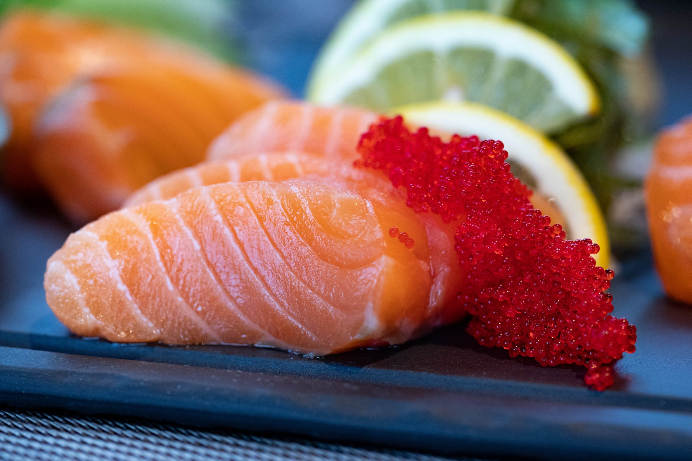 Plated salmon sashimi with fish eggs and slices of lemon.