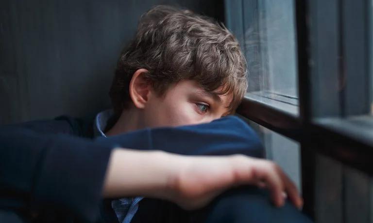 Boy Looking Out Window