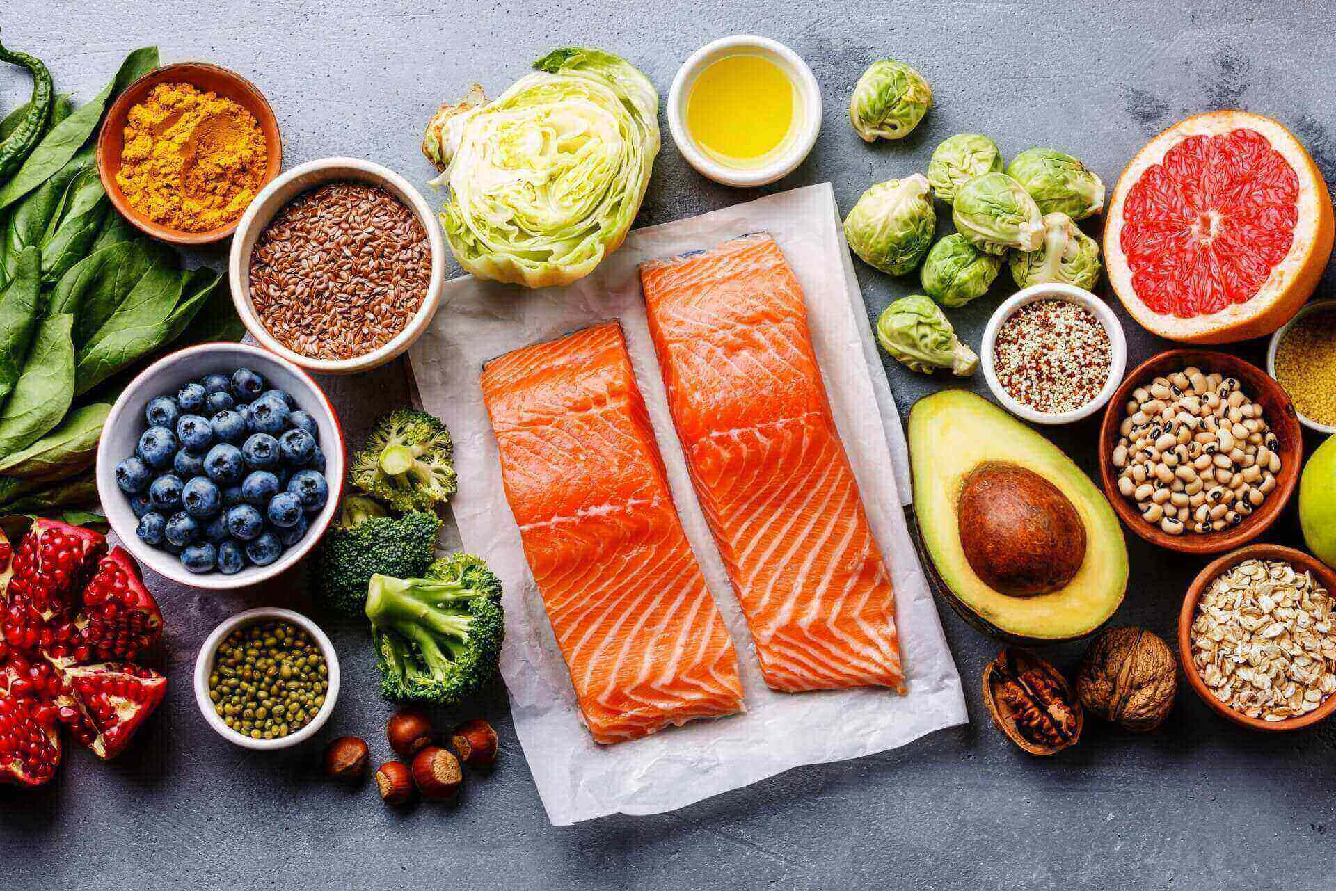 There is an array of food spread out on a counter top. The food includes blueberries, a head of lettuce chopped in half, fish, broccoli, and nuts.