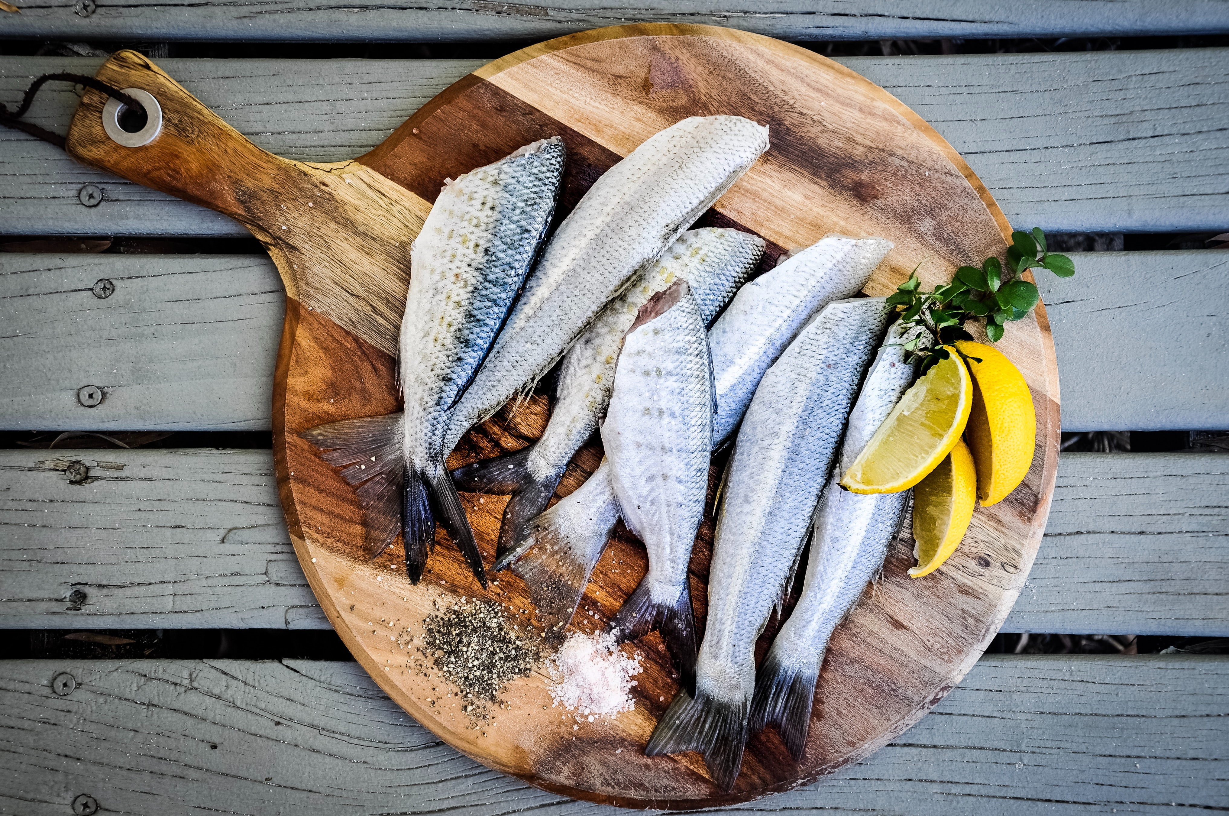 A brown wooden platter is set on a grey wooden table, zoomed in. On the platter are several fish, some cut lemons, loose salt and pepper, and an herb.