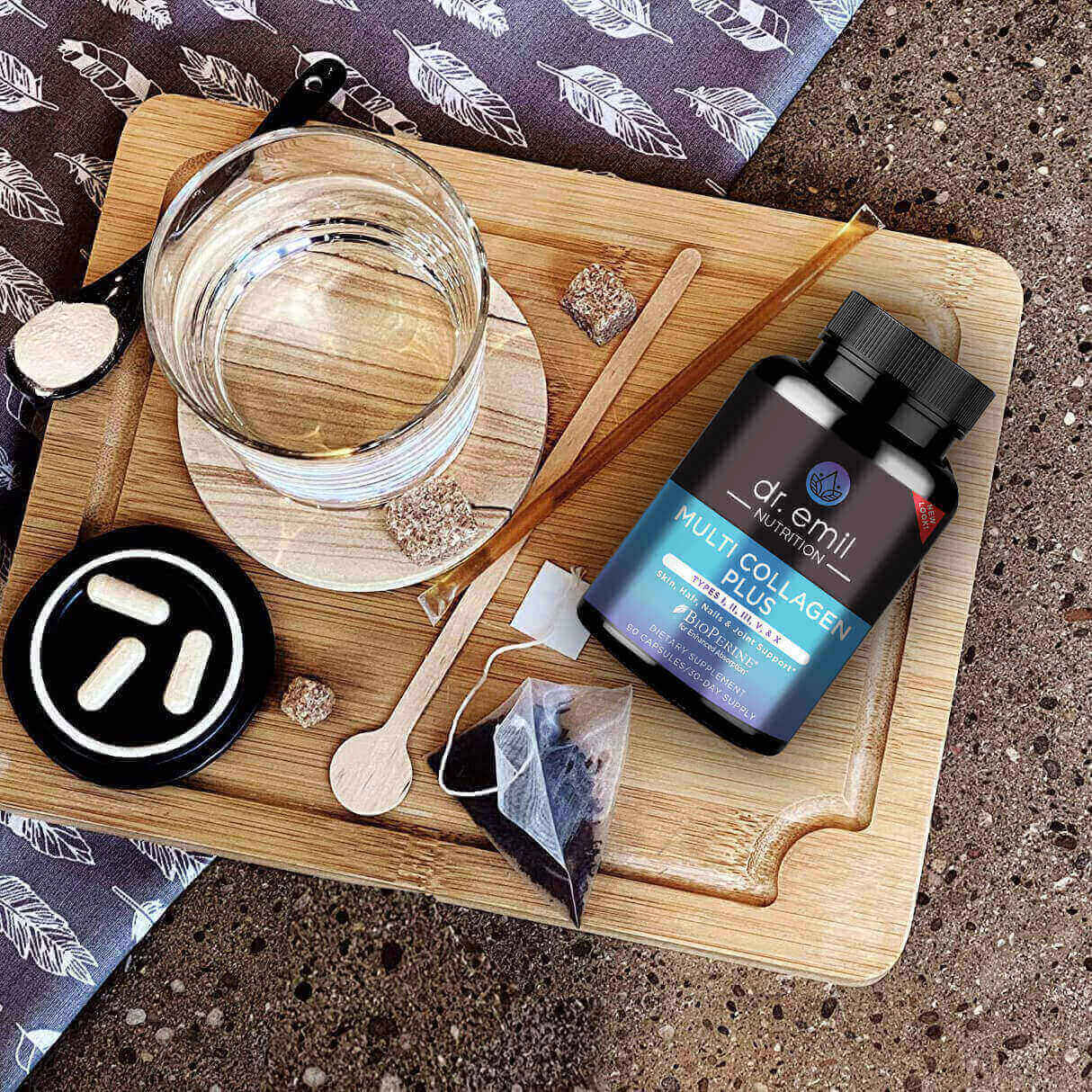 On a wooden cutting board is a cup of water on a coaster, a spoon with powder in it, a stick of honey, three pills on a black tray, and a bottle of collagen supplements.