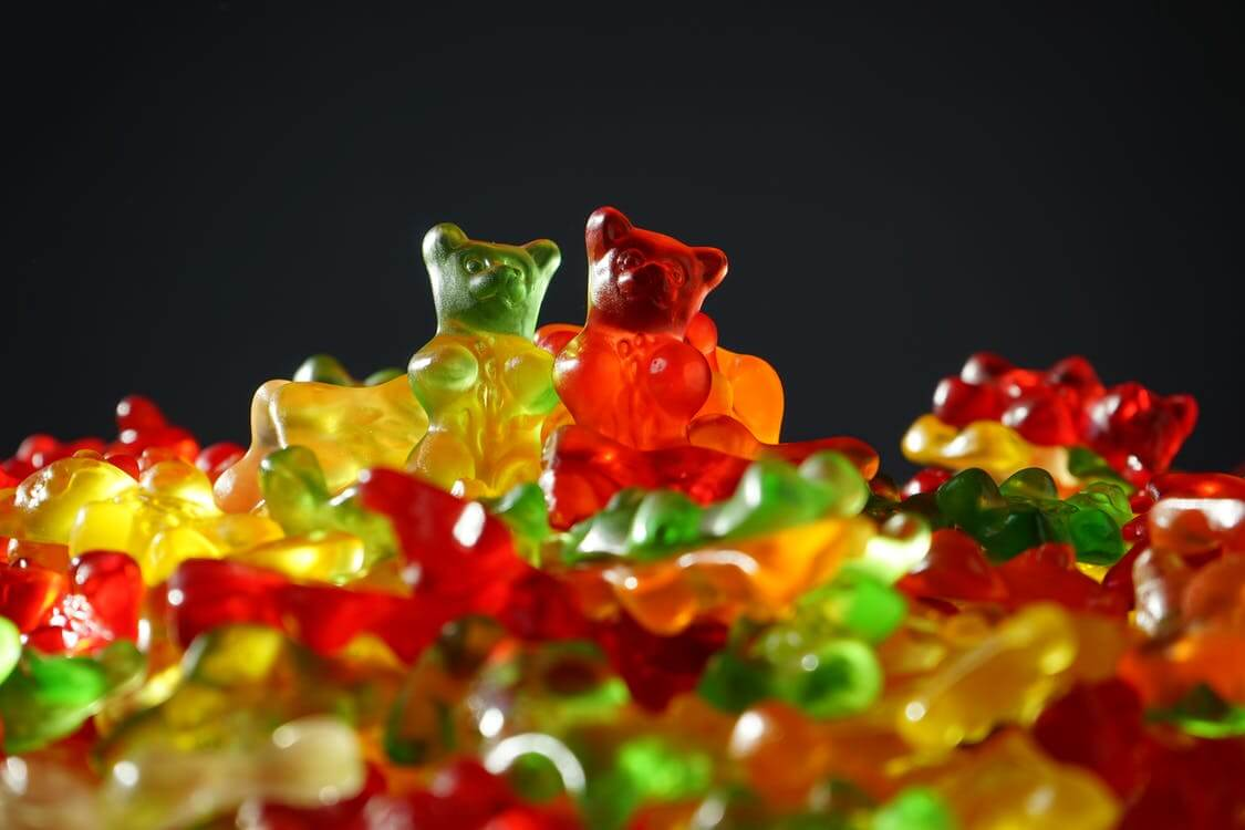 A black background, in front of which is a large pile of gummy bears. There is a yellow and a red bear sitting atop the pile.