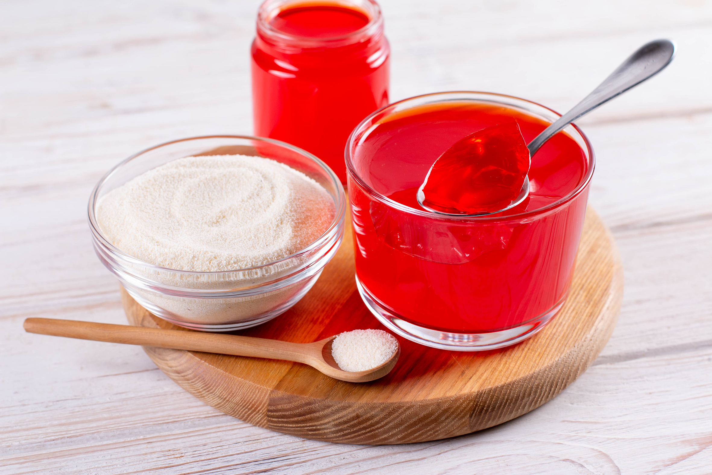 On a wooden serving tray is a wooden spoon with white powder, a glass bowl with white powder, and two glass containers with red gelatin, one has a silver spoon in it.