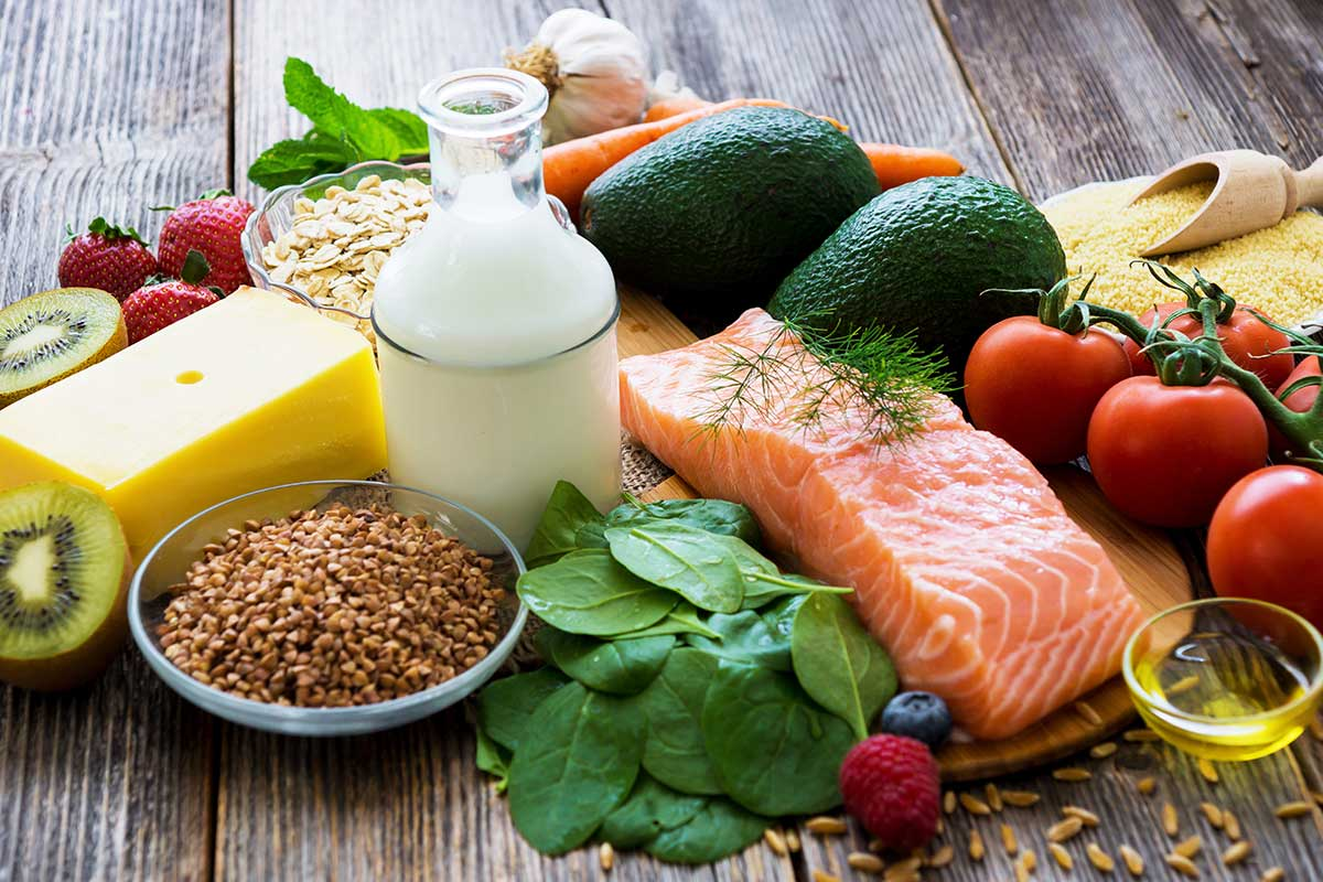 Several foods are laid out on a wooden table including a milk jug, fish, tomatoes, spinach, fruit, cheese, and oats.