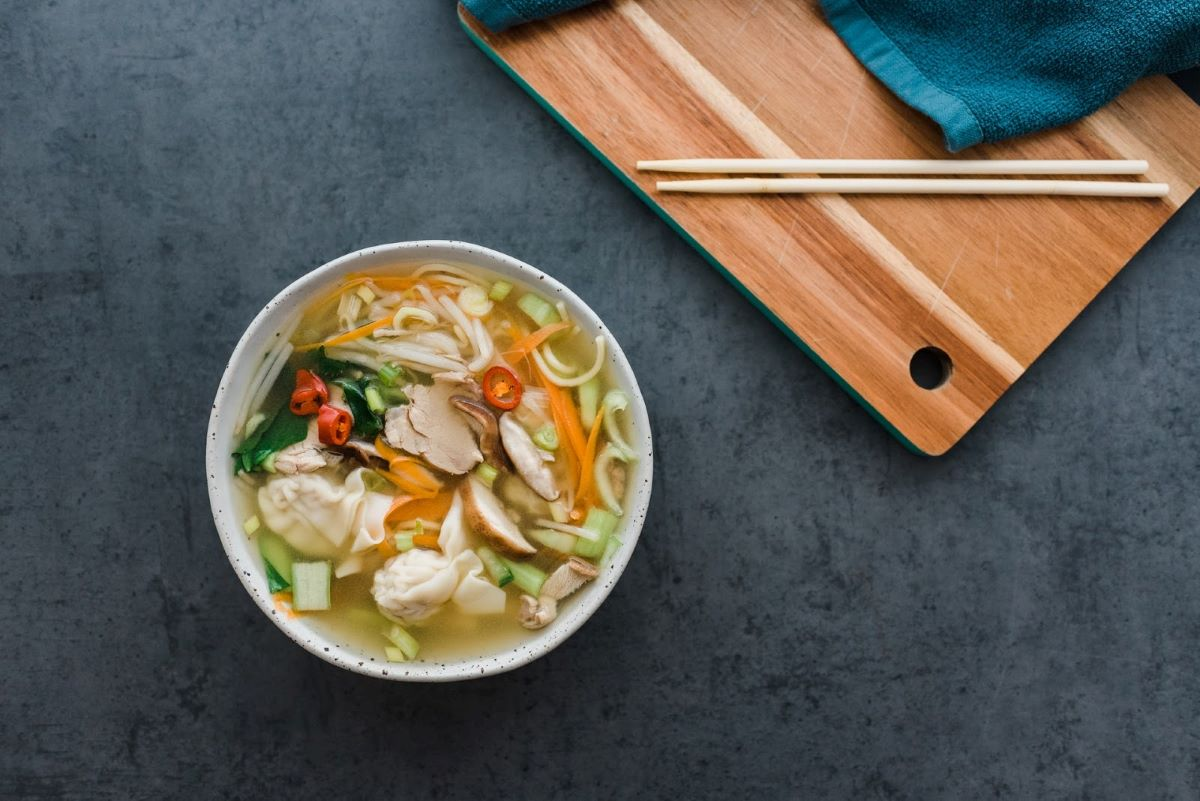 Bowl of bone broth with noodles and vegetables