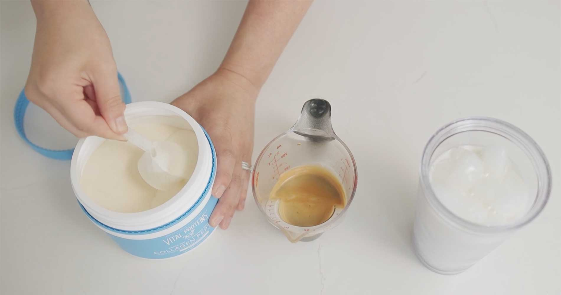 A hand holding a measuring cup is scooping up some collagen powder next to a glass of iced coffee ingredients.