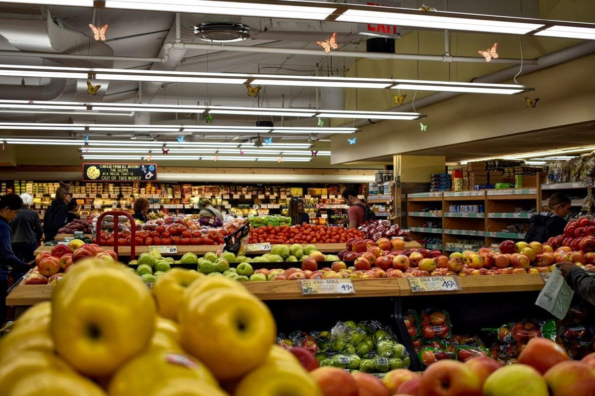 Close up of Apples with a Large Produce Section in the Background