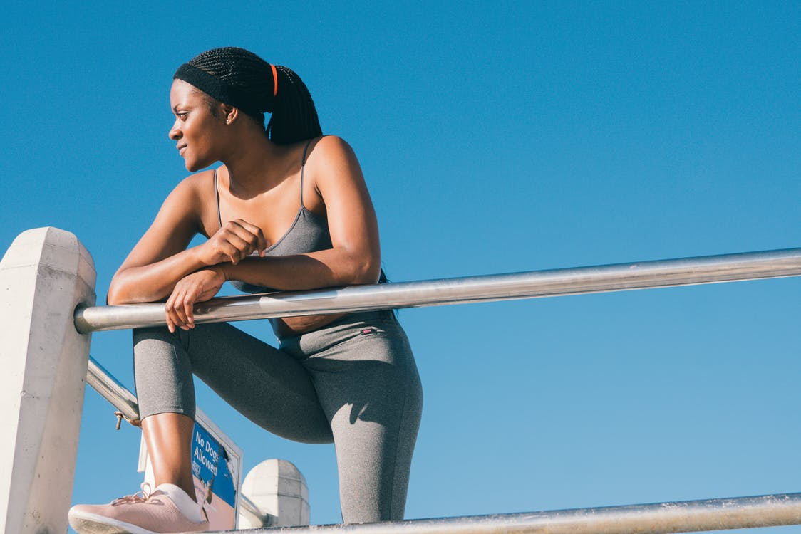A women in workout gear stands at the edge of a building.