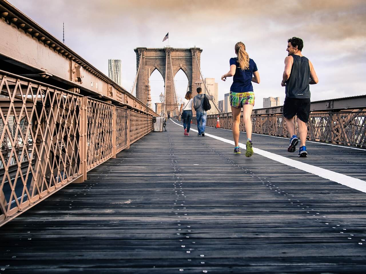 A couple is running on a bridge.
